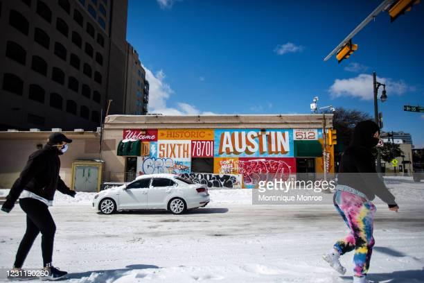 Pedestrians walk on along a snow-covered street on February 15, 2021 in Austin, Texas. Winter storm Uri has brought historic cold weather to Texas,...