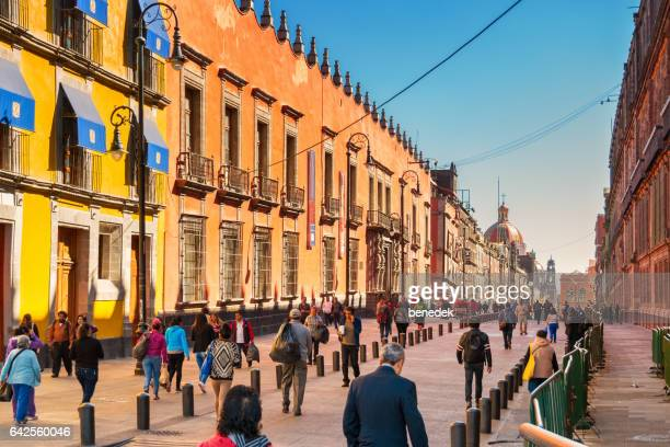 pedestrians walk on calle moneda at zocalo downtown mexico city - mexico city stock pictures, royalty-free photos & images