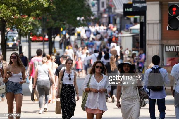 Pedestrians walk on Oxford street in central London on July 19, 2021 as coronavirus restrictions are lifted. - England lifts virtually all of its...