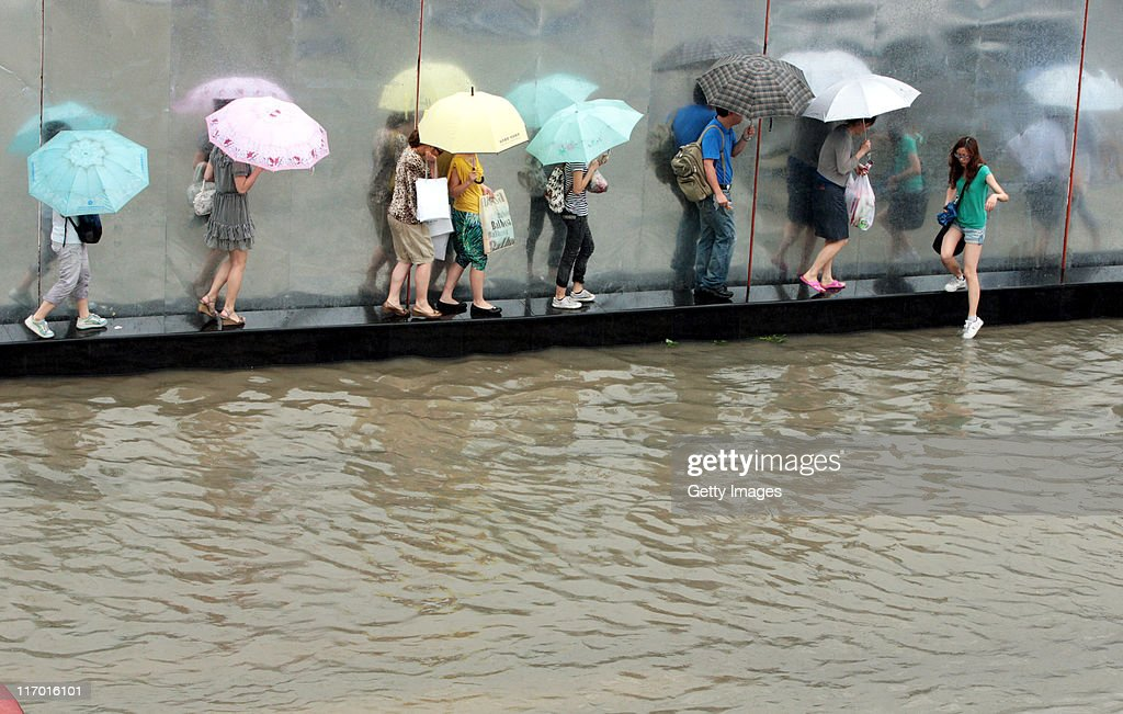 Pedestrians walk on the isolation belt after heavy rainfall on June 18, 2011 in Wuhan, Hubei Province of China. A heavy rainstorm hit Wuhan on Saturday, causing flooding across the region.