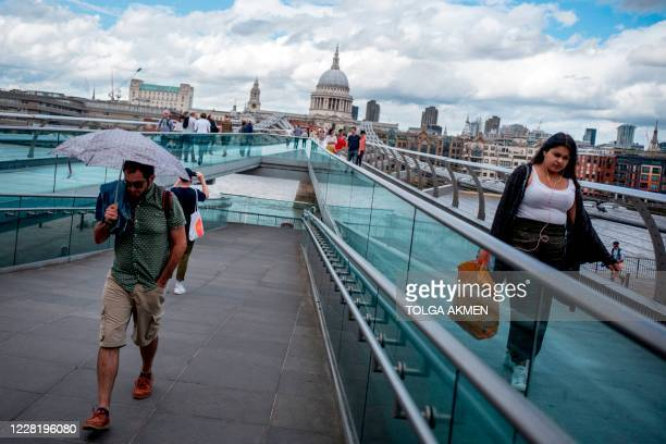 Pedestrians walk onto the Millennium Bridge in central London on August 24 2020 For those tourists who do run the gauntlet of Britain's...
