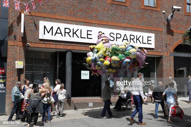Pedestrians walk outside a branch of retailer Marks and Spencer that has changed the name sign on the facade to Markle and Sparkle in honour of the...