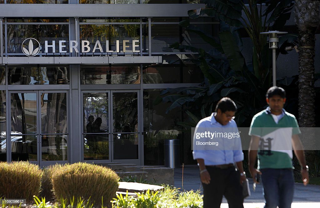 Pedestrians walk outside of the Herbalife Ltd. corporate headquarters in Torrance, California, U.S., on Thursday, Jan. 10, 2013. Daniel Loeb is squaring off against Bill Ackman over the future of Herbalife Ltd. By taking an 8.2 percent stake in the direct seller of nutrition shakes, Loeb's Third Point LLC is the latest firm to reject hedge fund manager Ackman's theory that Herbalife is a pyramid scheme. Photographer: Patrick Fallon/Bloomberg via Getty Images