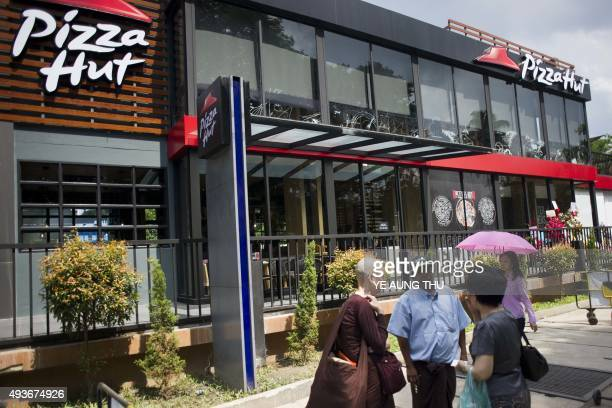 Pedestrians walk outside Pizza Hut's first restaurant in Yangon on October 22 2015 Pizza Hut is to open its first restaurant in Yangon the latest...