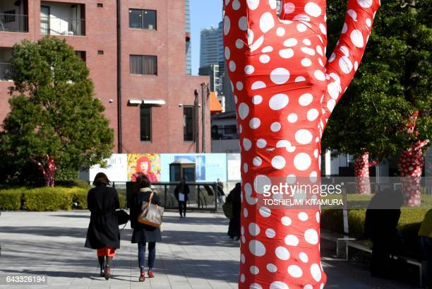Pedestrians walk outside the Japanese artist Yayoi Kusama's art exhibition titled My Eternal Soul at the National Art Center in Tokyo on February 21...