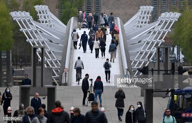 Pedestrians walk over the Millennium Bridge in the City of London on April 29, 2021. - Britain has been the European country worst-hit by the virus,...