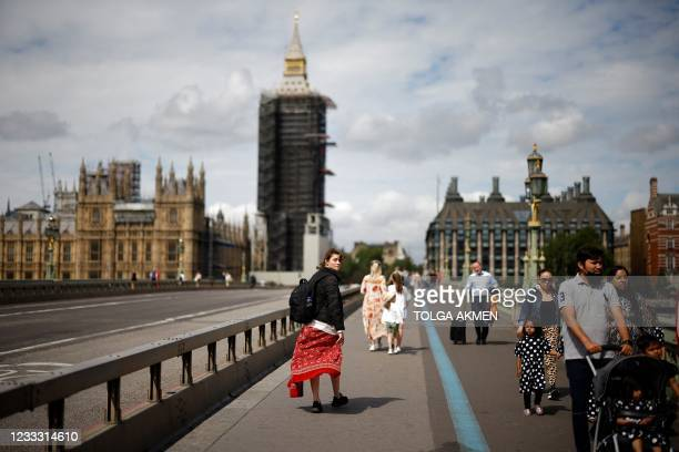 Pedestrians walk over Westminster Bridge near the Houses of Parliament in central London on June 7, 2021. - The Delta variant of the coronavirus,...