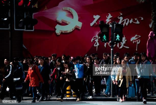 Pedestrians walk pass a Party propaganda poster in Shanghai on March 27, 2018. / AFP PHOTO / Johannes EISELE
