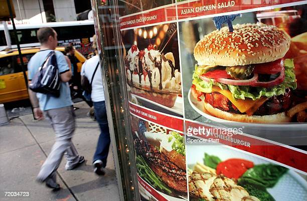 Pedestrians walk pass a sign displaying ice cream and hamburgers September 28 2006 in New York City Some critics are blaming New Yorks administration...