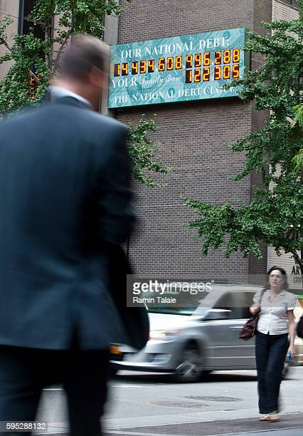 Pedestrians walk pass the National Debt Clock billboard on a building in midtown Manhattan on August 2 2011 in the New York City The national debt...