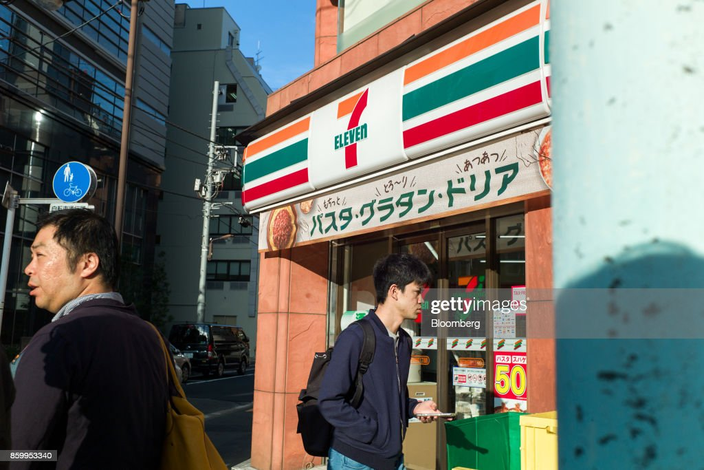 Pedestrians walk past a 7-Eleven convenience store, operated by Seven & i Holdings Co., in Tokyo, Japan, on Friday, Oct. 6, 2017. Seven & i is scheduled to report its second-quarter earnings results on Oct. 12. Photographer: Kentaro Takahashi/Bloomberg via Getty Images