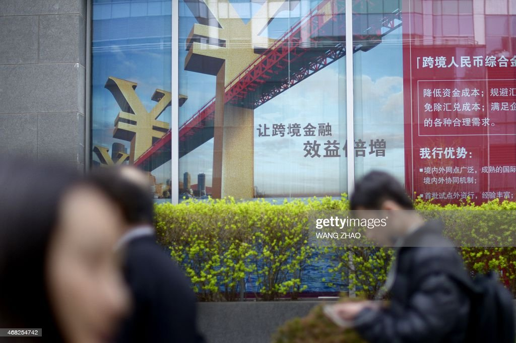 Pedestrians walk past a bank in a Central Business District (CBD) in Beijing on April 1, 2015. China scored a diplomatic coup by enticing almost 50 countries including key US allies to join its new development bank, but analysts say authoritarian Beijing now faces a daunting task managing a multilateral institution for the first time, with members ranging from the Netherlands to Nepal.