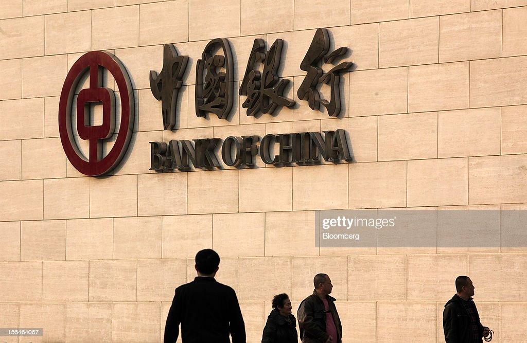 Pedestrians walk past a Bank of China Ltd. branch in Beijing, China, on Thursday, Nov. 15, 2012. Bank of China, the nation's fourth-largest lender by market value, last month posted a 17 percent increase in third-quarter profit, beating analyst estimates as it broadened its lending margin and economic growth curbed defaults. Photographer: Tomohiro Ohsumi/Bloomberg via Getty Images