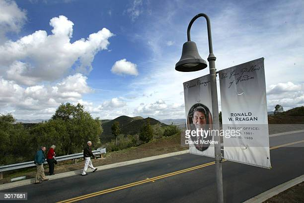 Pedestrians walk past a banner of former US President Ronald Reagan near the Ronald Reagan Presidential Library and Museum February 26 2004 in Simi...