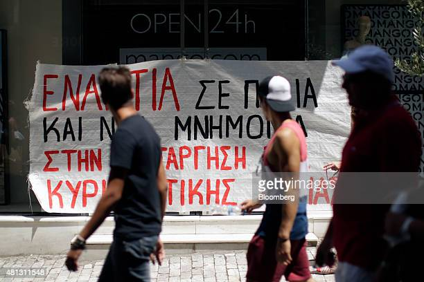 Pedestrians walk past a banner taped to the front of a clothing store which demonstrates against stores opening and trading on Sundays in Athens...