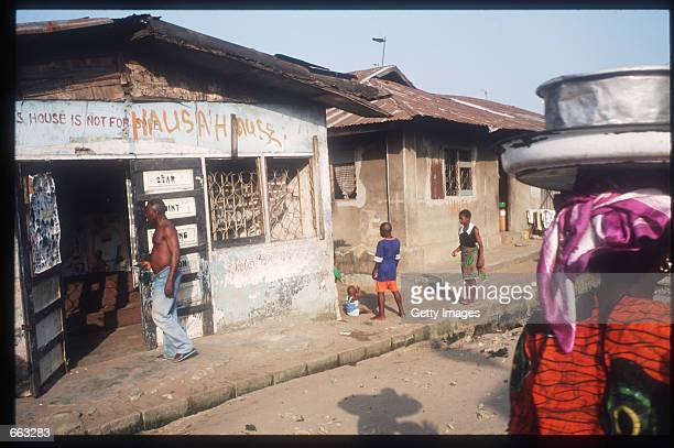 Pedestrians walk past a barber shop December 15 1999 in the Ajegunle area of Lagos Nigeria The signs on the shop indicate that the owner is a member...