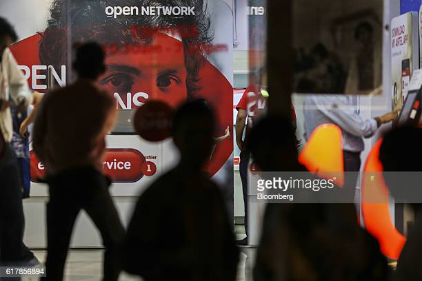 Pedestrians walk past a Bharti Airtel Ltd store in Mumbai India on Monday Oct 24 2016 Bharti Airtel is scheduled to release secondquarter earnings...