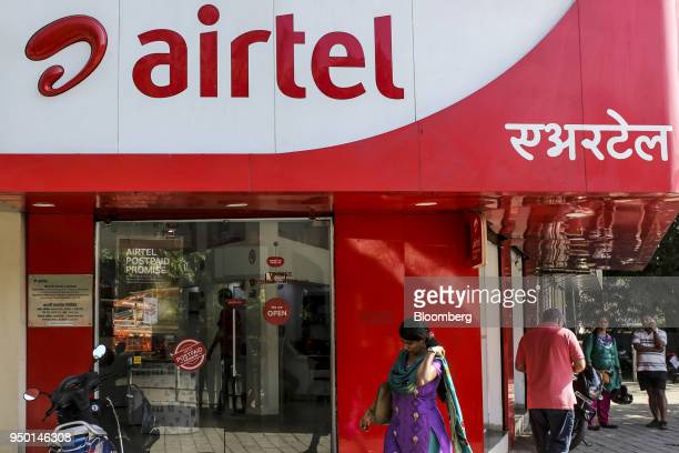 Pedestrians walk past a Bharti Airtel Ltd store in Mumbai India on Saturday April 21 2018 Bharti Airtel are scheduled to release earnings on April 24...