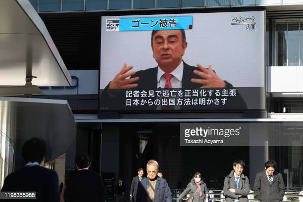 Pedestrians walk past a big screen showing images of former Nissan Motor Co Chairman Carlos Ghosn in a news program on January 09 2020 in Tokyo Japan...