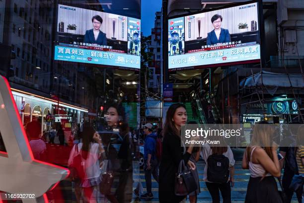 Pedestrians walk past a big screen television replaying Hong Kong Chief Executive Carrie Lam announcing the formal withdrawal of the extradition bill...