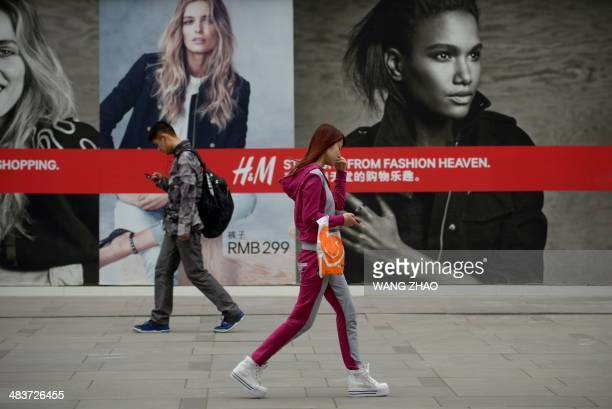 Pedestrians walk past a billbord outside a mall in the central business district in Beijing on April 10 2014 Chinese exports and imports fell sharply...