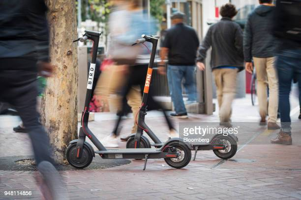 Pedestrians walk past a Bird Rides Inc left and Skinny Labs Inc SpinBikes shared electric scooters parked on Market Street in San Francisco...