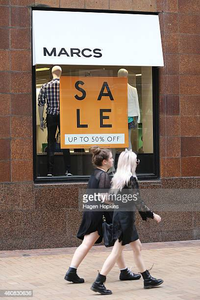 Pedestrians walk past a Boxing Day sale sign at Marcs clothing store on December 26 2014 in Wellington New Zealand Boxing Day is one of the busiest...