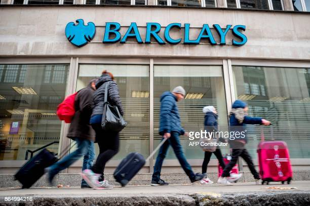Pedestrians walk past a branch of Barclays bank in central London on October 22 2017 / AFP PHOTO / AFP PHOTO AND Tolga Akmen / Tolga Akmen