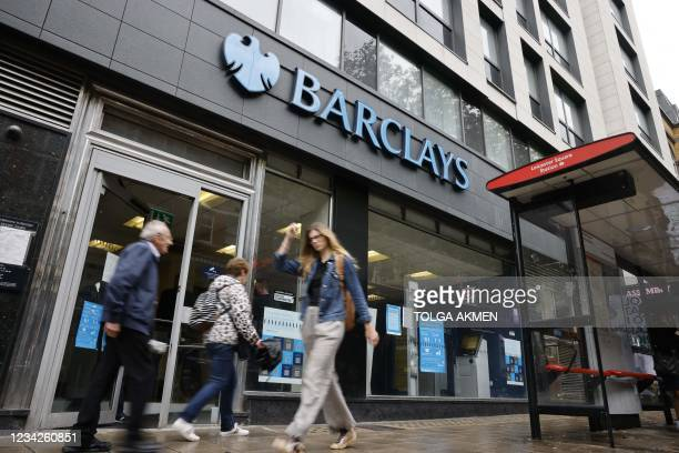Pedestrians walk past a branch of British bank Barclays in central London on July 28, 2021. - British bank Barclays said Wednesday that first-half...