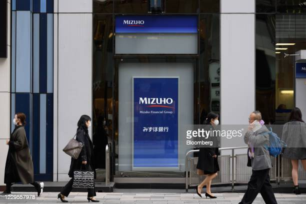 Pedestrians walk past a branch of Mizuho Bank Ltd. In Tokyo, Japan, on Monday, Nov. 9, 2020. Japanese banks expect business opportunities from...
