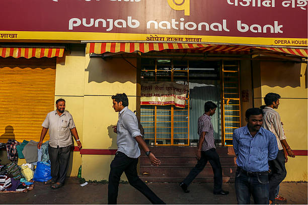 Pedestrians walk past a branch of Punjab National Bank in Mumbai India on Saturday Oct 19 2013 Volatility in Indias rupee fell to a twomonth low on...