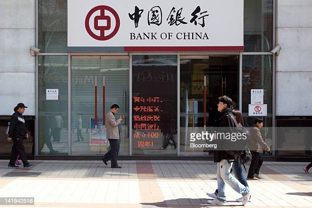 Pedestrians walk past a branch of the Bank of China Ltd in Beijing China on Tuesday March 27 2012 Bank of China is expected to announce earnings on...