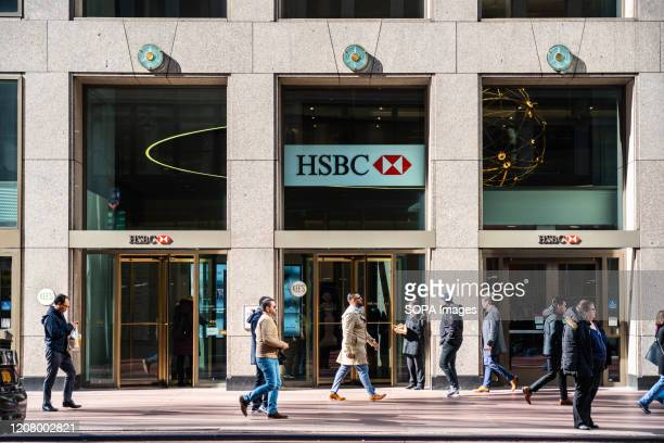 Pedestrians walk past a branch of the British multinational banking and financial services holding company, The Hongkong and Shanghai Banking...