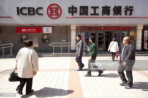 Pedestrians walk past a branch of the Industrial and Commercial Bank of China Ltd in Beijing China on Tuesday March 27 2012 ICBC is expected to...