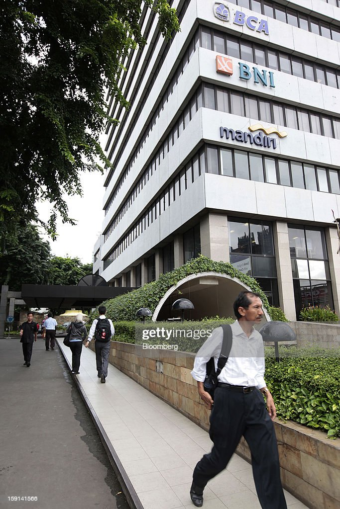 Pedestrians walk past a building housing the offices of PT Bank Central Asia (BCA), PT Bank Negara Indonesia (BNI) and PT Bank Mandiri in the financial district of Jakarta, Indonesia, on Tuesday, Jan. 8, 2013. Indonesia's rupiah weakened by the most in six months on concern the government's failure to meet its spending target last year will hamper economic growth and damp demand for local assets. Photographer: Dimas Ardian/Bloomberg via Getty Images