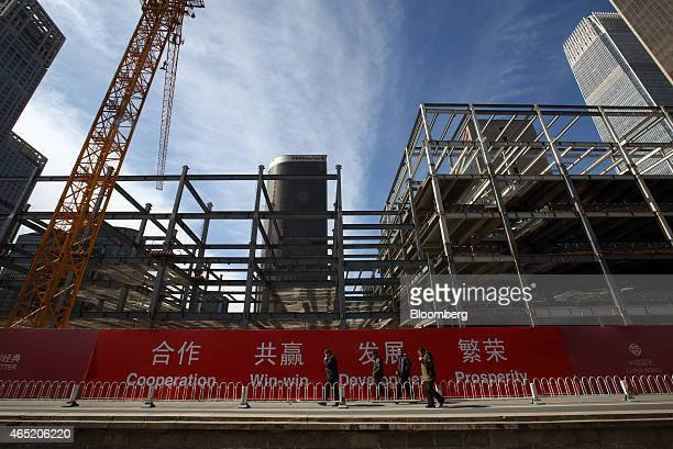 Pedestrians walk past a building under construction in the central business district of Beijing China on Wednesday March 4 2015 China's leaders are...