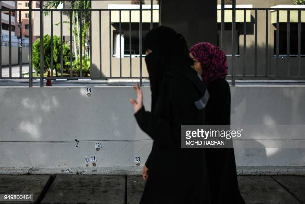 Pedestrians walk past a bulletriddled wall at the scene where Palestinian scientist Fadi Mohammad alBatsh was gunned down April 21 in what his family...