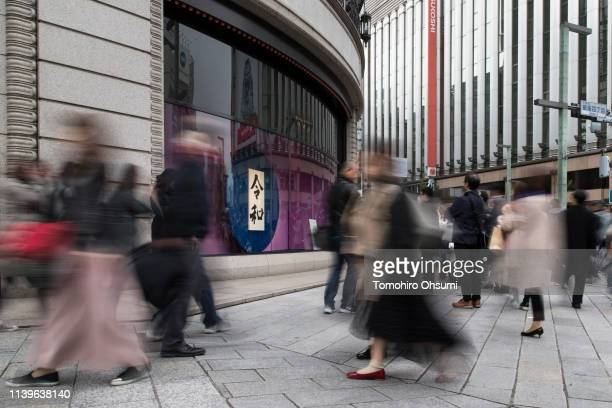 Pedestrians walk past a calligraphy work showing the name of Japan's next imperial era 'Reiwa' displayed in the Ginza district on April 01 2019 in...