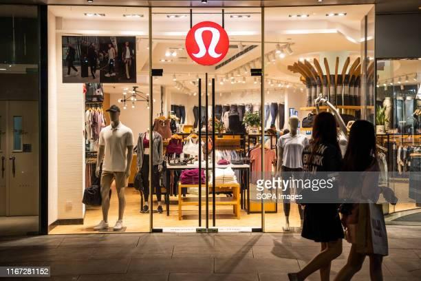 Pedestrians walk past a Canadian athletic apparel retailer Lululemon store in Shanghai.