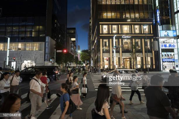Pedestrians walk past a Cartier store operated by Cie Financiere Richemont SA at night in the Ginza area of Tokyo Japan on Tuesday Aug 21 2018 Japan...