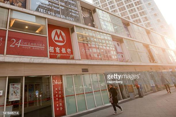 Pedestrians walk past a China Merchants Bank Co Ltd branch in Beijing China on Tuesday March 27 2012 China Merchants Bank is expected to announce...