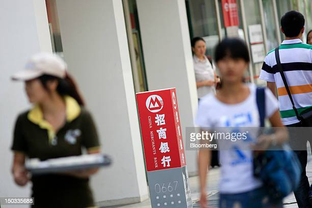 Pedestrians walk past a China Merchants Bank Co Ltd branch in Beijing China on Thursday Aug 16 2012 China Merchants Bank is expected to announce...