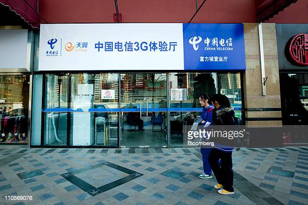 Pedestrians walk past a China Telecom Corp store in Beijing China on Tuesday March 22 2011 China Telecom the country's biggest fixedline carrier said...