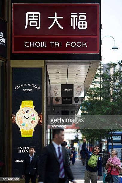 Pedestrians walk past a Chow Tai Fook Jewellery Group Ltd store in the shopping district of Tsim Sha Tsui in Hong Kong China on Tuesday Nov 26 2013...