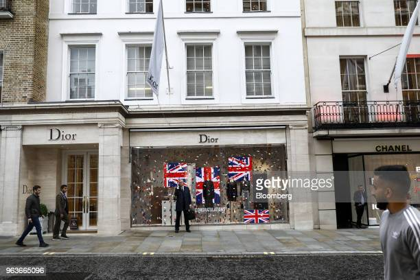 Pedestrians walk past a Christian Dior SE luxury store as a businessman makes a phone call on New Bond Street in London UK on Tuesday May 29 2018 UK...