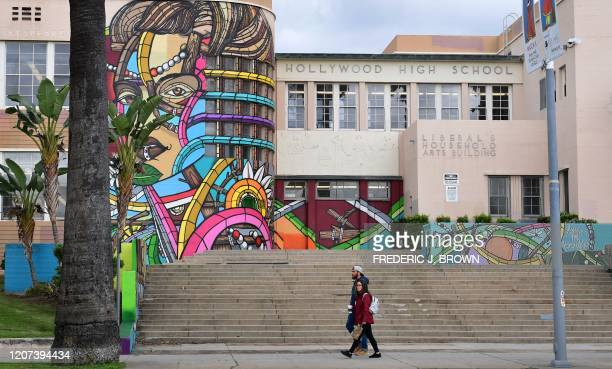 Pedestrians walk past a closed Hollywood High School in Hollywood, California on March 16, 2020 as the Coronavirus pandemic brings much of California...