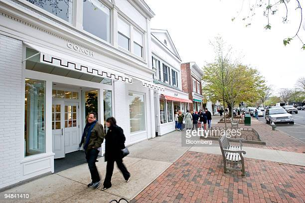 Pedestrians walk past a Coach store on Main Street in East Hampton New York US on Saturday May 3 2008 With the weak dollar and lure of beaches...