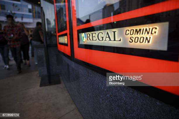 Pedestrians walk past a 'Coming Soon' sign displayed outside the box office of the Regal Entertainment Group Regal Cinemas LA LIVE Stadium 14 movie...