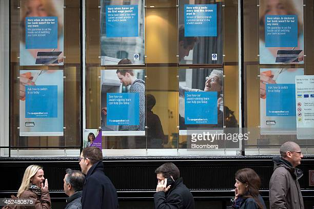 Pedestrians walk past a CoOperative Bank Plc bank branch in London UK on Friday Nov 29 2013 CoOperative Bank Plc which is trying to plug a 15...
