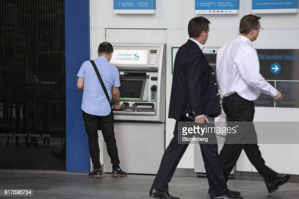 Pedestrians walk past a customer using an automated teller machine outside a Standard Chartered Plc bank branch in the central business district of...